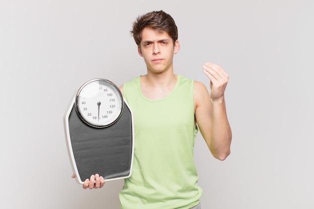 Rapaz fazendo capice ou gesto de dinheiro, mandando você pagar suas dívidas! conceito de escala