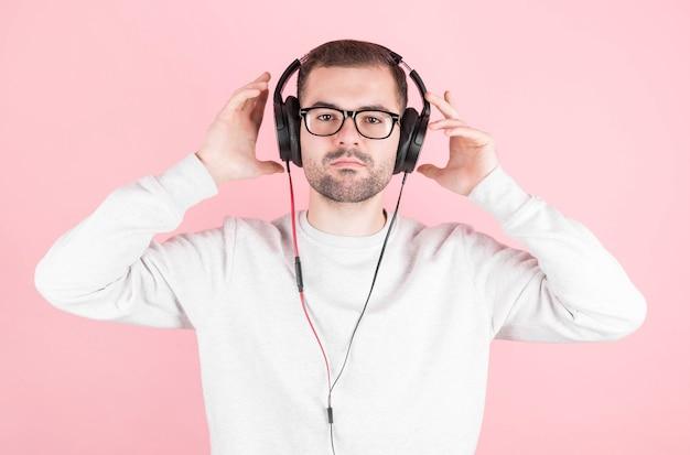 Rapaz feliz e fofo ouve música em grandes fones de ouvido brancos em uma parede rosa, segura-os, em um moletom branco, com um sorriso radiante, dia mundial do dj