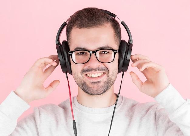 Rapaz feliz e fofo ouve música em grandes fones de ouvido brancos sobre um fundo rosa, segura-os, em um moletom branco, com um sorriso