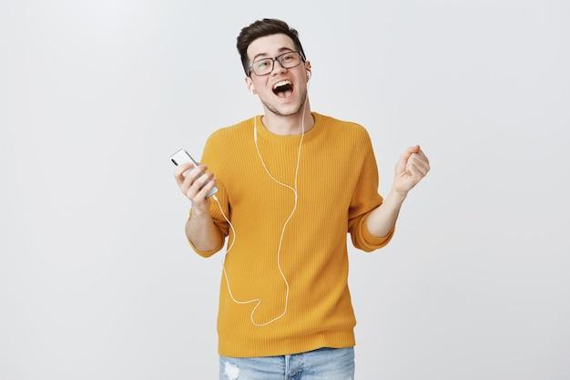 Rapaz feliz ouvindo música nos fones de ouvido e cantando despreocupado