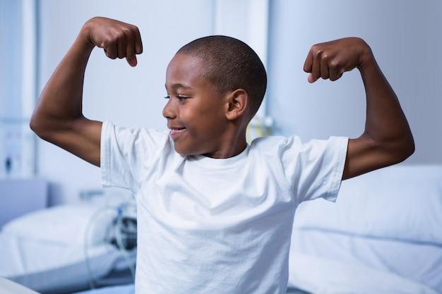 Rapaz, flexionando seus músculos na enfermaria