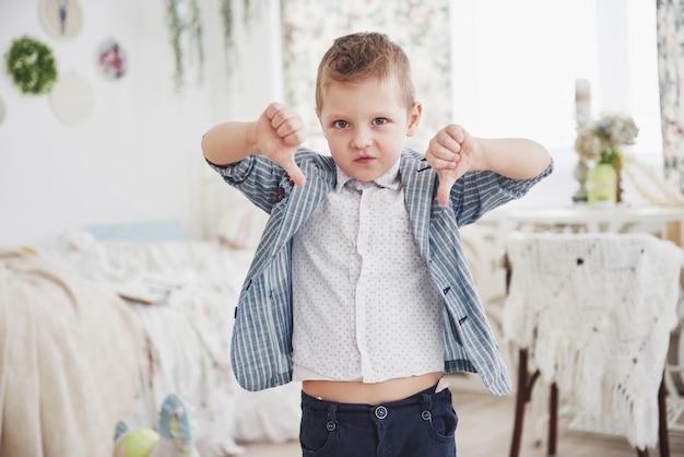 Rapaz gesticula o dedo para baixo. conceito de emoção. mostra sua atitude em relação a aulas e escolas