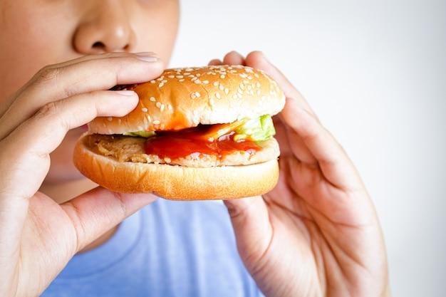 Rapaz gordo asiático come hambúrgueres. conceitos alimentares que causam problemas físicos à saúde das crianças causando doenças fáceis, como a obesidade.
