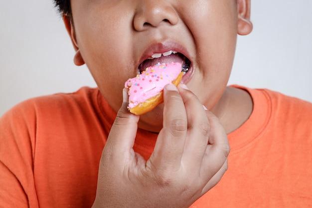 Rapaz gordo asiático segurando um donut coberto de morango