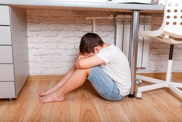 Rapaz jovem adolescente pré-adolescente caucasiano abraçando seu joelho, cobrir o rosto. cyber bullying em criança, saúde mental infantil deprimida.