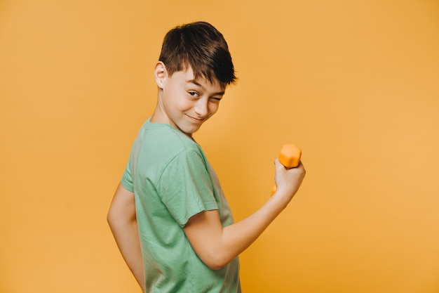 Rapaz jovem alegre, vestido com uma camiseta verde, piscadelas e fazendo exercícios com halteres para melhorar seu estado físico conceito de pessoas ativo e otimista.