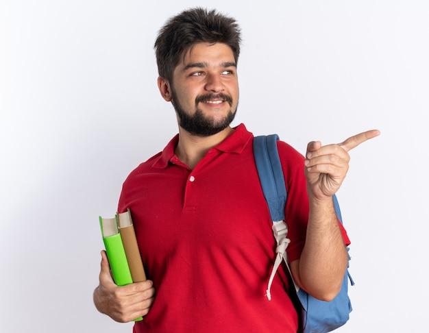 Rapaz jovem barbudo feliz e positivo com uma camisa pólo vermelha com mochila segurando notebooks olhando para o lado apontando com o dedo indicador para o lado em pé