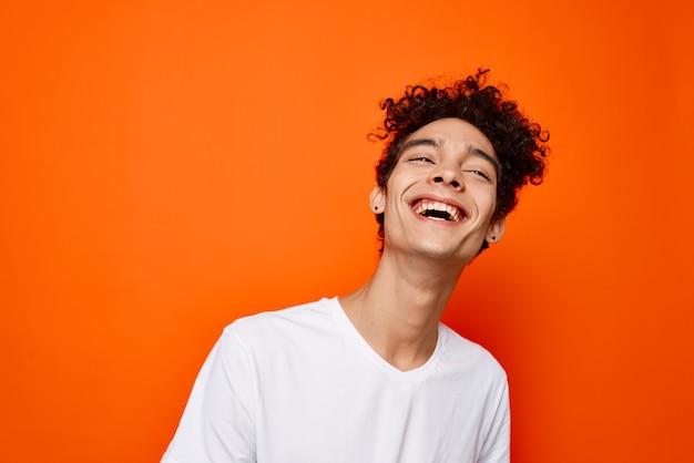 Rapaz jovem com camiseta branca, cabelo encaracolado e sorriso laranja na parede