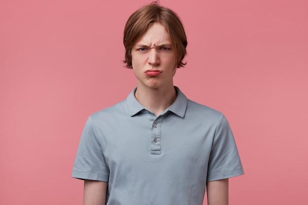Rapaz jovem cuidadosamente penteado insatisfeito, sobrancelhas franzidas, olhos agressivos com raiva, vestido com uma camiseta pólo casual, isolado sobre um fundo rosa
