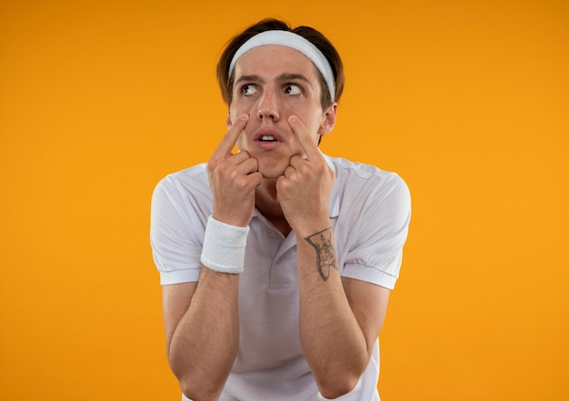 Rapaz jovem e desportivo descontente com uma faixa na cabeça e uma pulseira puxando as pálpebras para baixo, isoladas na parede laranja