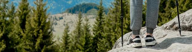Rapaz jovem e despreocupado, subindo enormes pedras sólidas, usando bastões para facilitar o acesso ao topo, apreciando a vista de maravilhas naturais no caminho