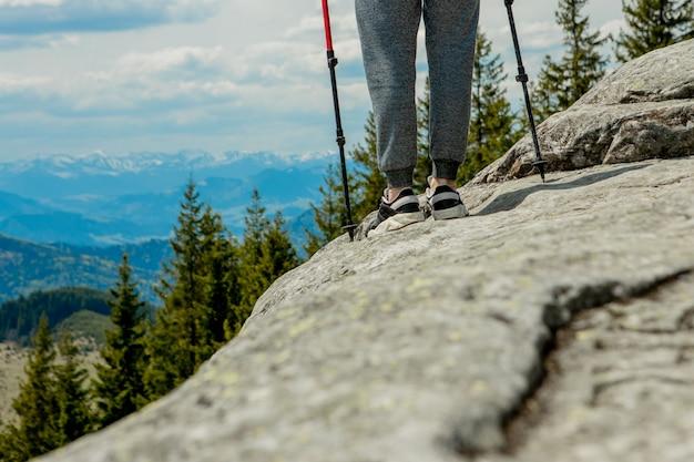 Rapaz jovem e despreocupado, subindo enormes rochas sólidas, usando bastões para facilitar o acesso ao topo, apreciando a vista de maravilhas naturais no caminho