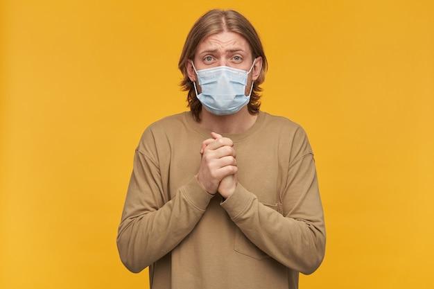Rapaz jovem e suplicante com cabelo loiro, barba e bigode. vestindo um suéter bege e máscara protetora médica. junta as palmas das mãos, perguntando. isolado sobre a parede amarela