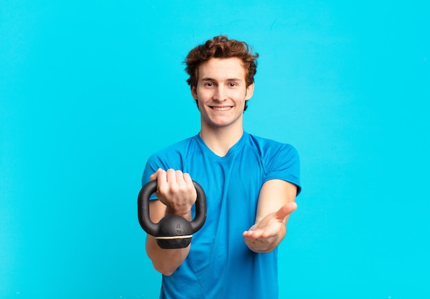 Rapaz jovem esporte sorrindo feliz com olhar amigável, confiante e positivo, oferecendo e mostrando um objeto ou conceito. conceito de haltere