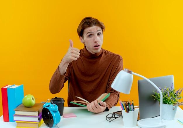 Rapaz jovem estudante a pensar sentado à secretária com ferramentas escolares a segurar o livro e o polegar para cima