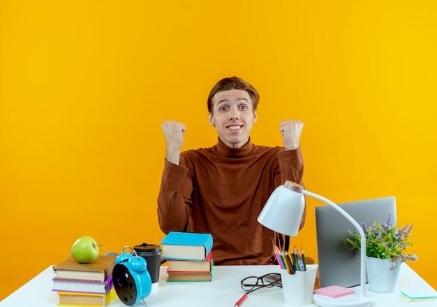 Rapaz jovem estudante satisfeito sentado à mesa com as ferramentas da escola, mostrando um gesto de sim isolado na parede amarela