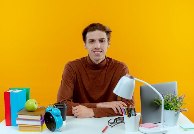 Rapaz jovem estudante satisfeito sentado à mesa com ferramentas escolares em amarelo