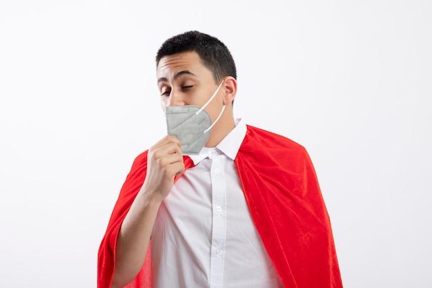 Rapaz jovem super-herói com capa vermelha usando máscara protetora segurando máscara tentando tirá-la com os olhos fechados, isolado no fundo branco