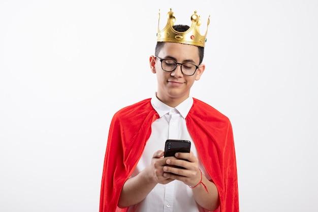 Rapaz jovem super-herói satisfeito com capa vermelha usando óculos e coroa, usando telefone celular isolado no fundo branco com espaço de cópia