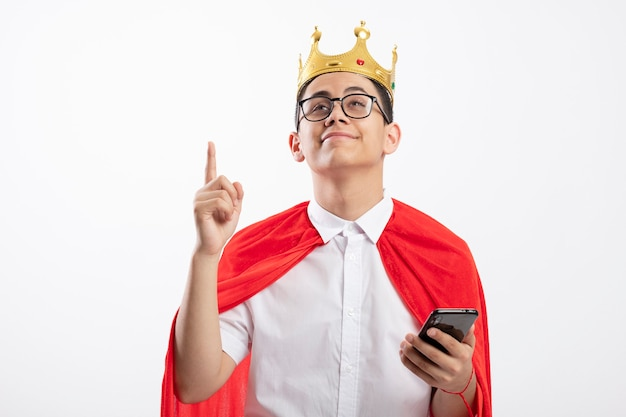 Rapaz jovem super-herói satisfeito com uma capa vermelha usando óculos, olhando para a câmera, segurando o celular apontando e olhando para cima, isolado no fundo branco com espaço de cópia