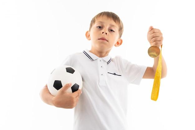 Rapaz jovem treinador europeu em uma camiseta branca segura uma bola de futebol e um apito contra branco