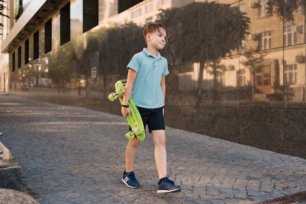 Rapaz legal da escola jovem com roupas brilhantes andando com penny board nas mãos