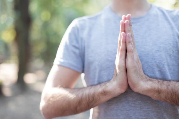 Rapaz meditando no pose da oração