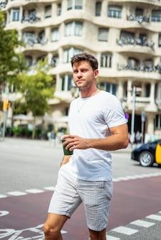 Rapaz moderno com bebida para levar na rua