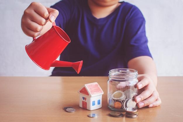 Rapaz, molhando a casa e moedas. planejar o conceito de casa