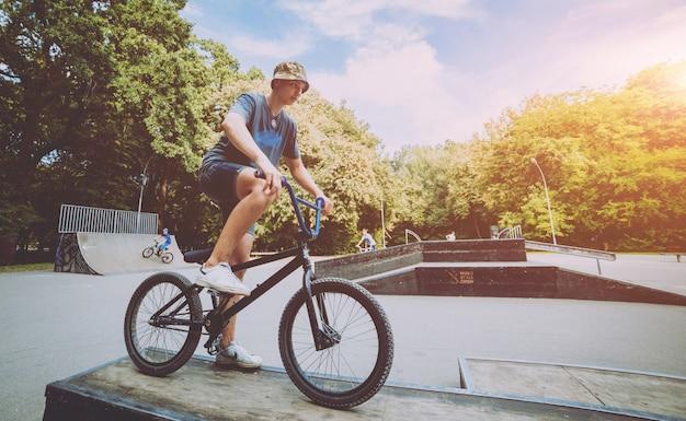 Rapaz, montando um bmx em um parque.