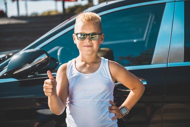 Rapaz mostra o polegar no fundo do carro