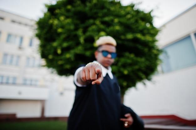 Rapaz muçulmano árabe elegante originalmente com cabelo e óculos de sol colocados nas ruas e mostra o dedo na câmera.