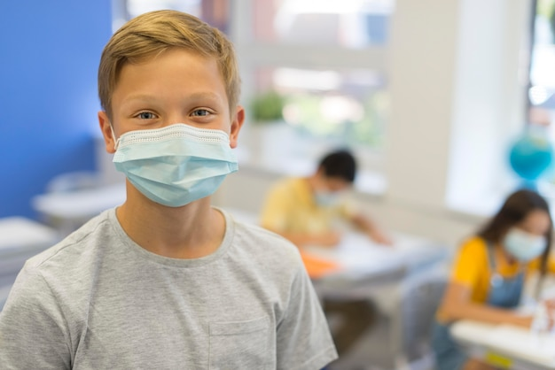 Rapaz na aula com máscara
