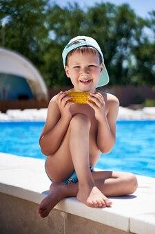 Rapaz na praia comendo milho na praia