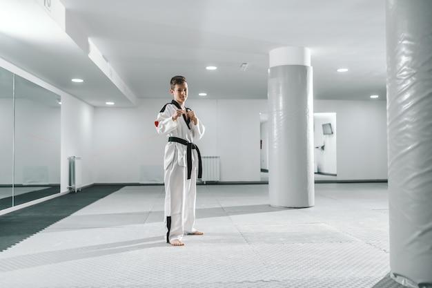 Rapaz no dobok em pé descalço, posando e olhando para a câmera. conceito de treinamento de taekwondo.