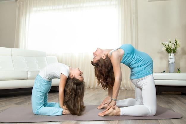 Rapaz nova fazendo yoga pré-natal com sua pequena filha