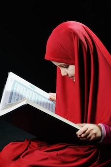 Rapaz nova muçulmana que lê o corão sagrado