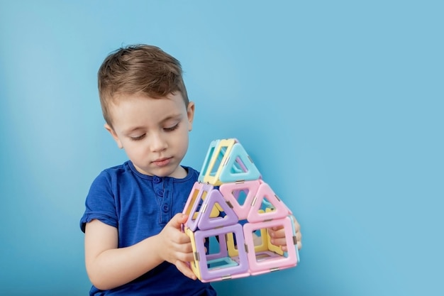 Rapaz olha através da forma no construtor de cores com a conexão dos ímãs