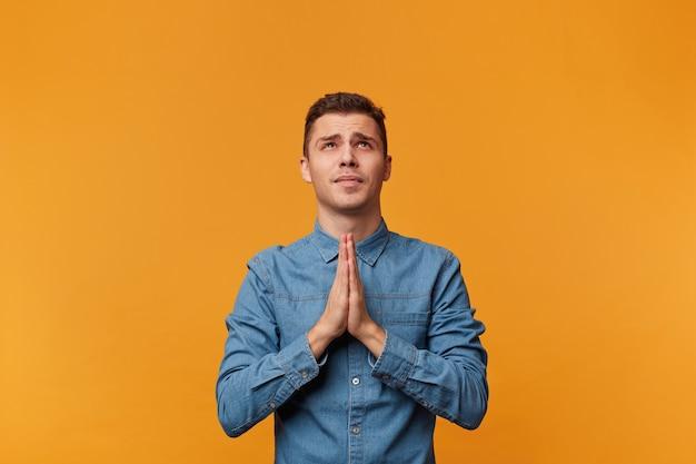 Rapaz olha para cima com esperança, as palmas das mãos cruzadas em um gesto de oração, pedindo ajuda de poderes superiores