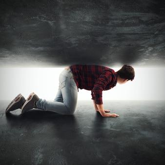 Rapaz olha para uma lacuna entre duas paredes com luz