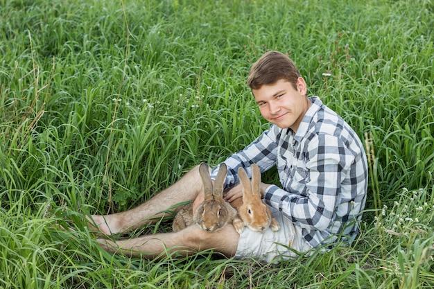 Rapaz, olhando para a câmera segurando coelhos