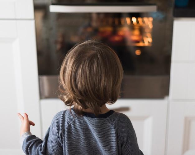 Rapaz olhando para o forno