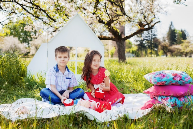 Rapaz pequeno à moda e menina encaracolado bonita em um piquenique. o conceito de infância e estilo de vida.