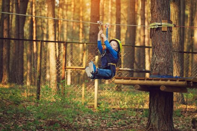 Rapaz pequeno alegre adorável que ziplining na floresta