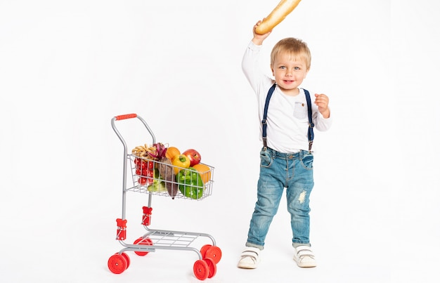 Rapaz pequeno alegre na roupa ocasional que está no estúdio com cesta de alimento saudável. compras, desconto, conceito de venda