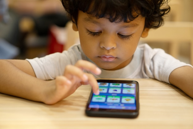 Rapaz pequeno asiático bonito está jogando um jogo no smartphone