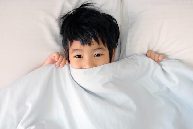 Rapaz pequeno asiático na cama que cobre sua cara com a cobertura ou a coberta branca. menino dormindo. criança dormindo