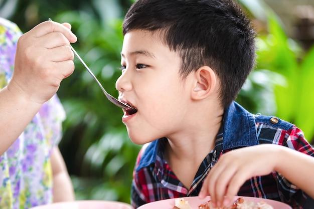 Rapaz pequeno asiático que come com alimento do arroz na tabela de madeira, alimento de alimentação do arroz da mãe