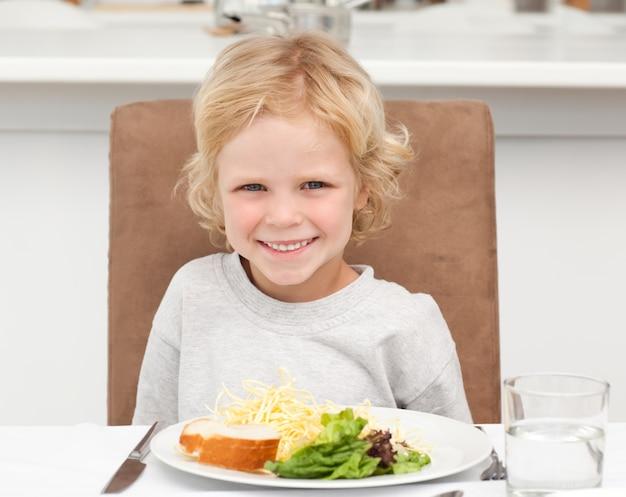 Rapaz pequeno bonito comendo macarrão e salada