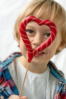 Rapaz pequeno bonito dentro com os pirulitos vermelhos dos doces na forma do coração, fundo branco. criança linda come doces. dia dos namorados, o conceito de amor.